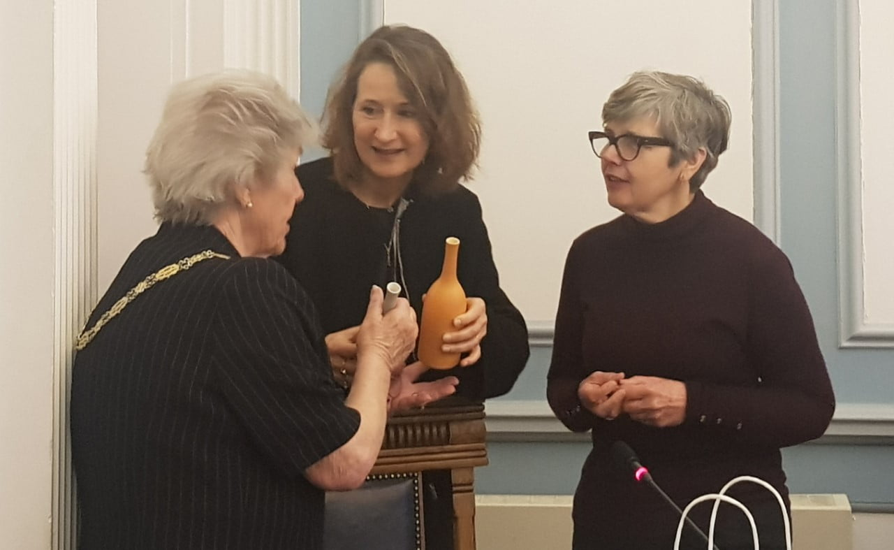 Three females talking. Two are holding ceramic bottles