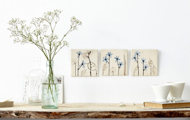 Three canvas paintings and a glass vase