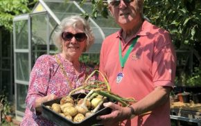 Man and woman holding a basket of potatoes and garlic. Greenhouse and trees in background
