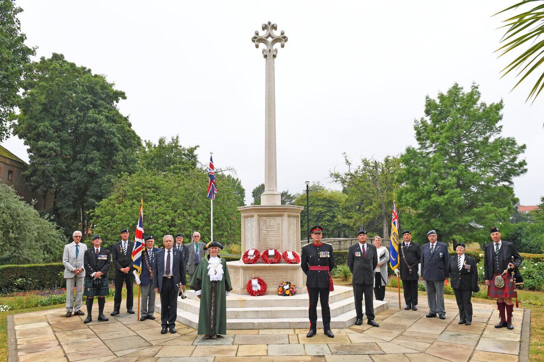 People standing around war memorial.