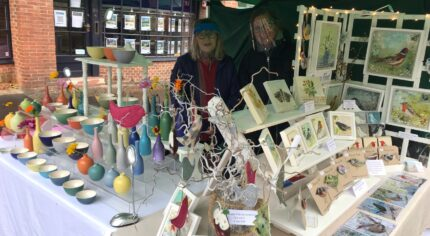 Two females standing behind a stall selling craft items.