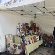 Market stall displaying cushions and craft items.