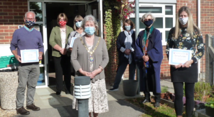 Group of people wearing masks and socially distancing.