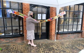 Female cuts a ribbon to mark the opening of a shop.