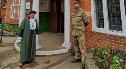 Mayor and solider standing in front of a red brick building.