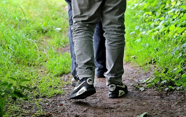 Trousered legs of two people walking in tandem along a footpath