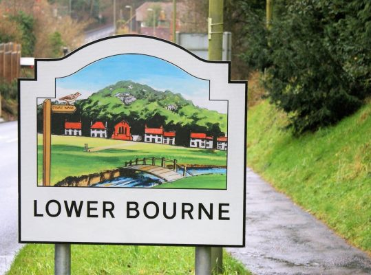 A village entry sign for Lower Bourne