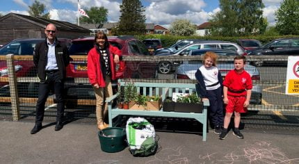 Two adults and two children standing next to a bench filled with items to make a hanging basket.