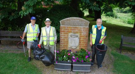 Three males in high viz jackets and holding black rubbish sacks.