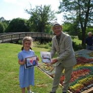 Young girl holds a drawing and receiving a prize from the Mayor.