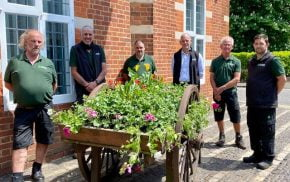 Six members of the Council's Outside workforce standing around the freshly planted hop cart outside the Council offices
