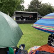Umbrellas in foreground and stage with band performing in background.