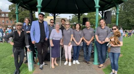 A group of people standing in front of a bandstand.