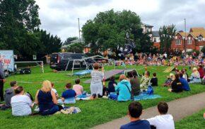 Crowd of people sitting on grass watching a stunt bike rider