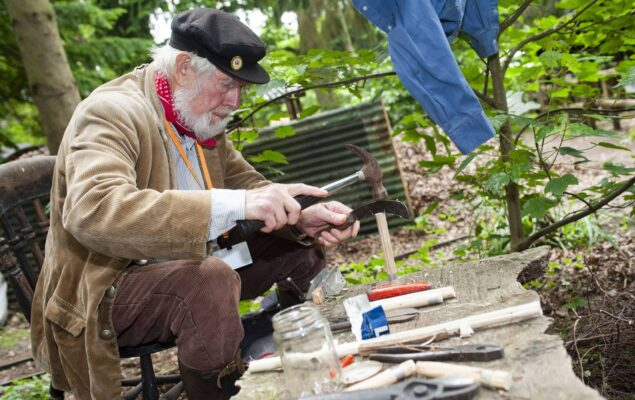 Older male splitting a piece of wood with a knife and hammer.