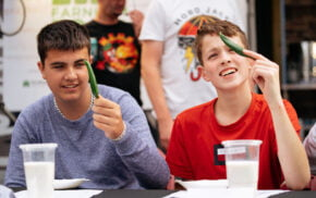Two young males each holding a green chilli